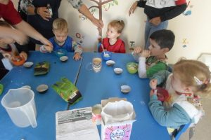 Four children, two boys and two girls, making Bhhafi, a sweet treat made with milk and coconut, with help from their teachers