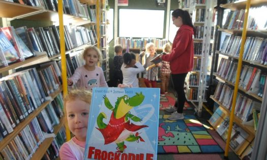Little girl holding up a book called Frockodile on a school bus that's been turned into a library on wheels. The little girl is accompanied by a teacher and other little children who are exploring the books on board the bus