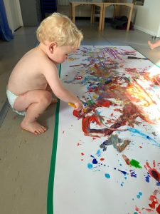 Boy toddler bending down to paint a canvas on the floor wearing a diaper