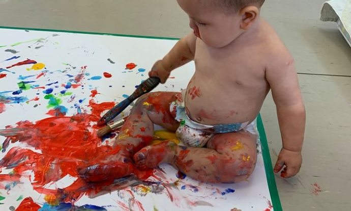 Toddler painting on a canvas on the floor in a diaper