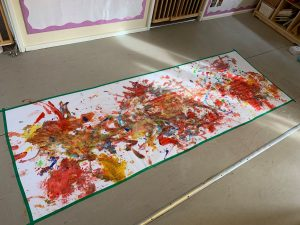 Canvas on the floor that's covered in paint from toddlers who painted it